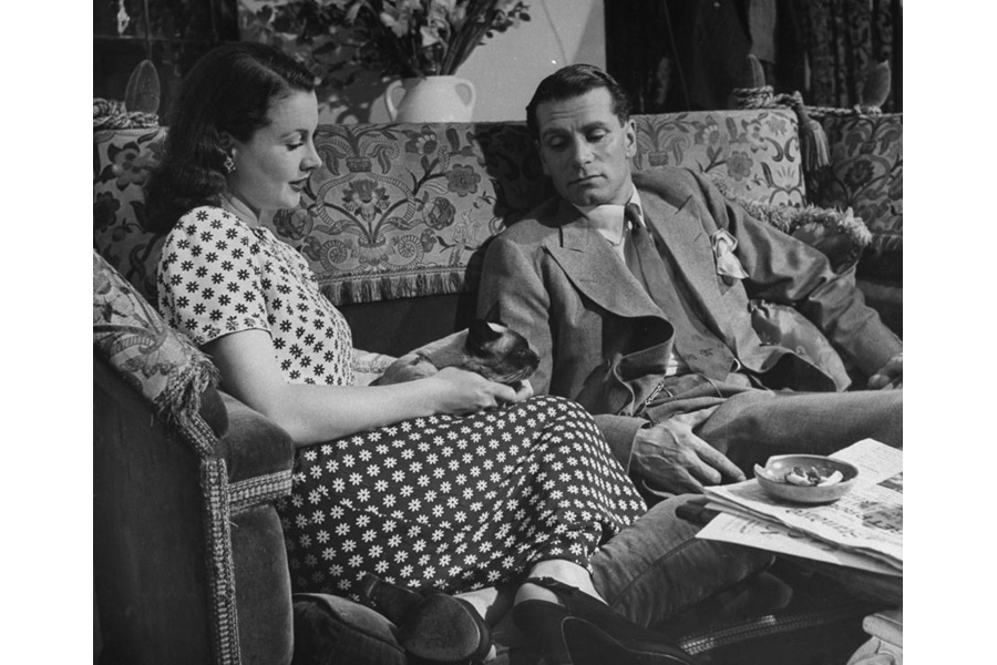 Vivien Leigh and Laurence Olivier lounging on a Knole Sofa with their Siamese cat, New Boy.