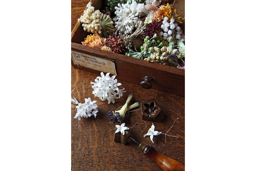 A drawer full of artificial seeds, ears and stamens. In the foreground are bunches of waxed orange blossom and jasmine petals. Photo credit: Alexis Lecomte
