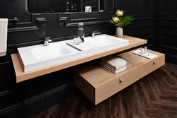 Characterized by a minimalist yet highly functional design, the DXV Modulus 55-inch lavatory, countertop slab and 36-inch wall mounted drawer seamlessly combine in a harmonious and customizable design. The collection's single handle faucets showcase a two-tone design with their contrasting decorative rings.