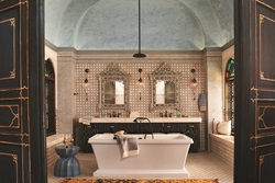"Kati Curtis, CID, blended traditional Moroccan tile and artwork with clean, contemporary fixtures and fittings to represent a ""Golden Era Getaway"" in Casablanca. Curtis selected the DXV Fitzgerald freestanding soaking tub and Keefe widespread bathroom faucets, both of which feature modern design lines that pop brilliantly against the handcrafted elements of the room."
